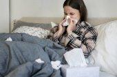 Kranke Frau im Bett Niesen