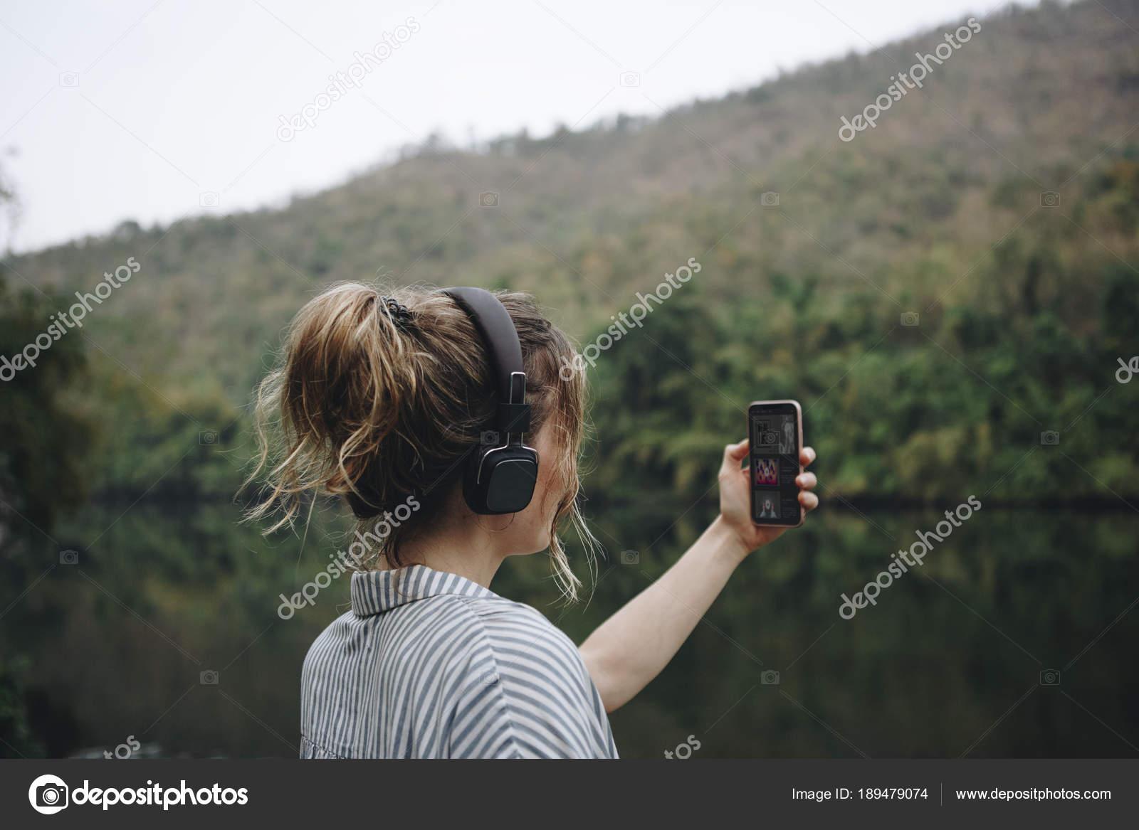 Femme seule dans la nature écouter de la musique avec des écouteurs et smartphone image de rawpixel