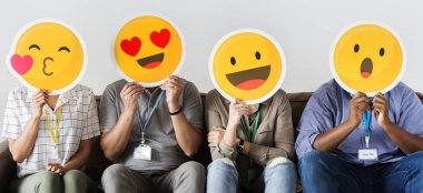 Group of people holding yellow emoticons