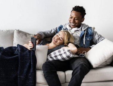Interracial couple on a couch listening to music