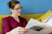 Kaukasische Frau liest Zeitung