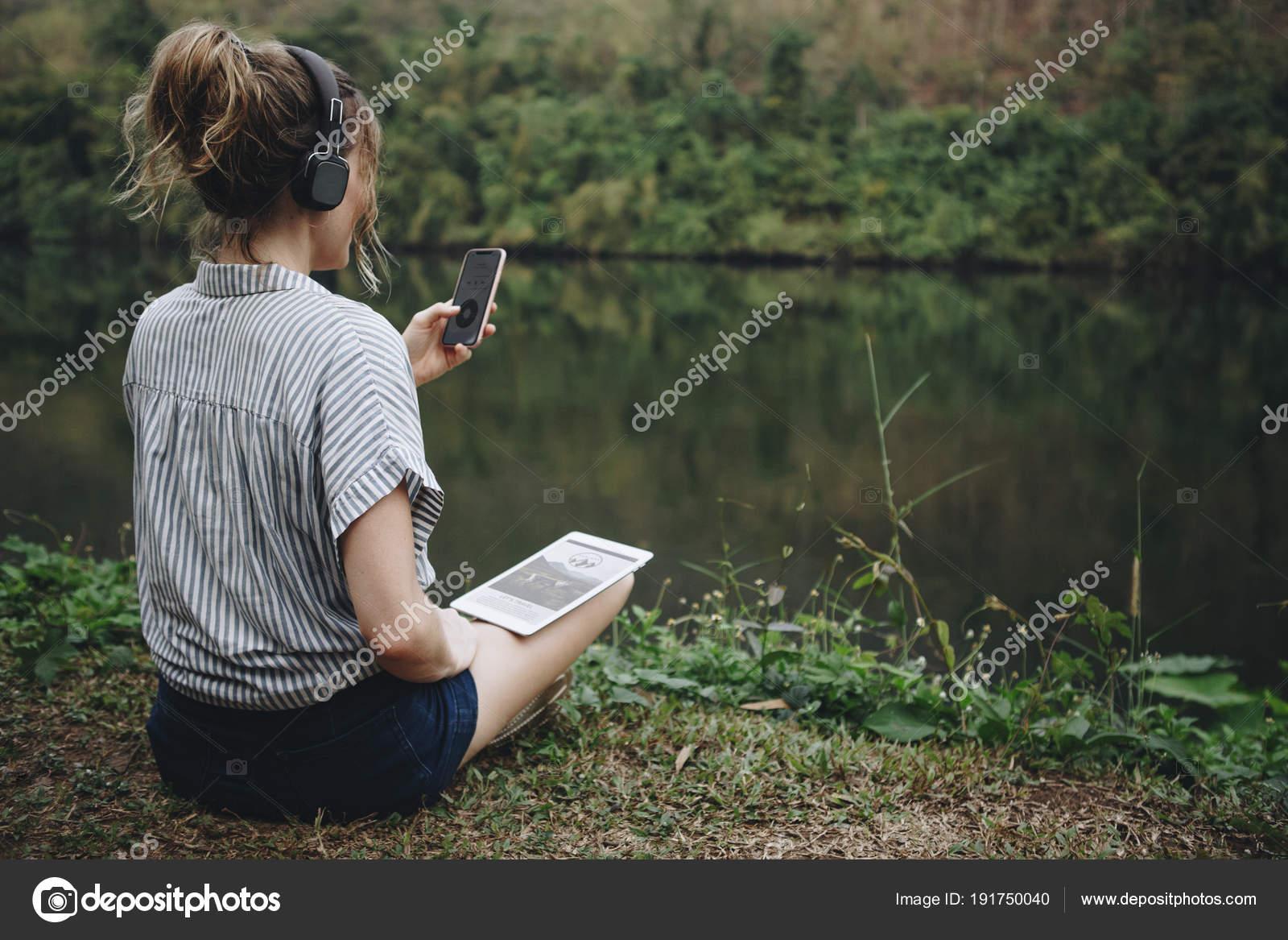 Woman alone nature listening music headphones digital tablet smartphone music stock photo