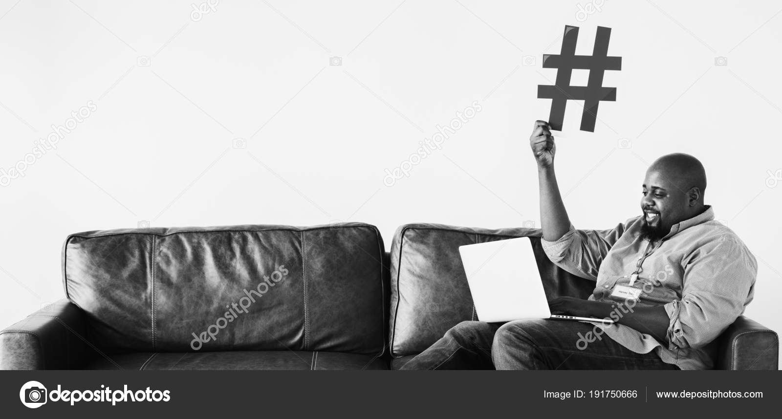 Black man relaxing on sofa and holding laptop with blue hashtag sign black and white photo by