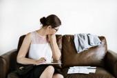 Geschäftsfrau arbeitet auf einer Couch