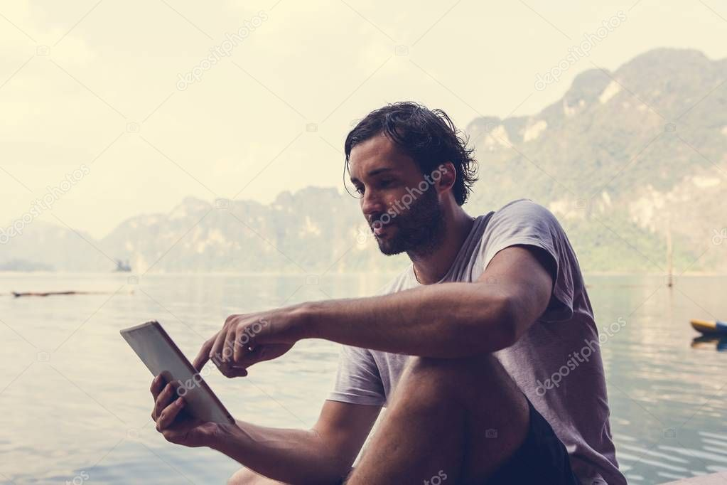 Man using his phone by a lake