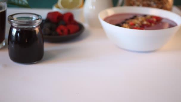 Ženská ruka dala talíř s čerstvým croissantem. Nedaleko černý rybíz džem a talíř s bobulemi. Koncept snídaně