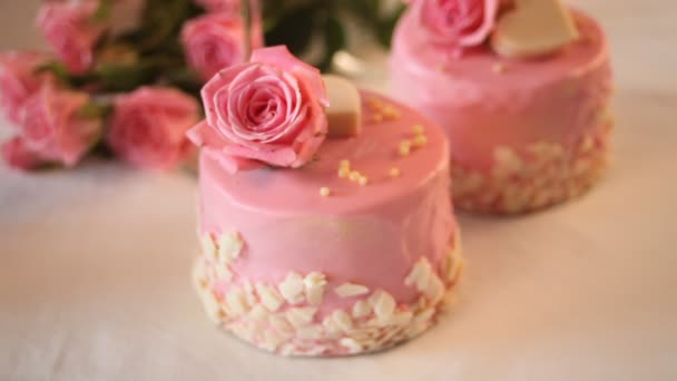 Woman hand decorating with heart shaped candy chocolate mini small cakes with pink glaze and beautiful roses