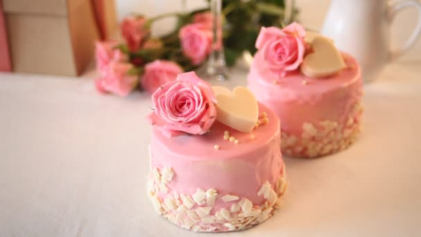 Woman hand put a cup of coffee nearby with mini small cakes with pink glaze, decorated beautiful roses