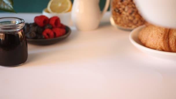 A nő keze egy gyümölcsös turmixtálat tett az asztalra. Croissant zsemle, egy pohár kávé a közelben
