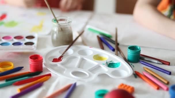 Akvarel, štětce, barevné tužky. Děti kreslí na pozadí
