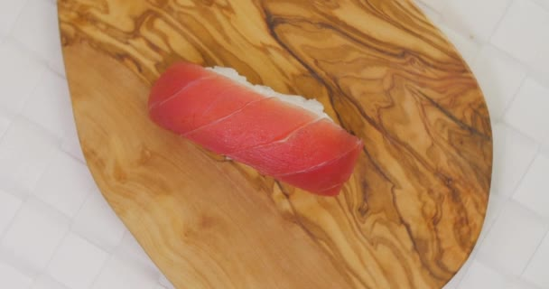 Nigiri tuna sushi rotating on wood