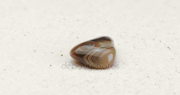 Měsíční kámen drahokam otočení na bílý písek