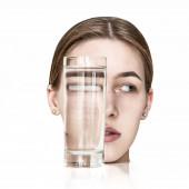 Tükröződik egy lány egy pohár vízben. Szokatlan kép vízzel.