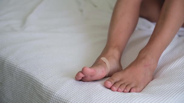 Zblízka opálená samice bosá na posteli. Noha v škrábancích. Mladá žena si přilepí náplasti na nohy. Zdravotní péče, zranění nohou