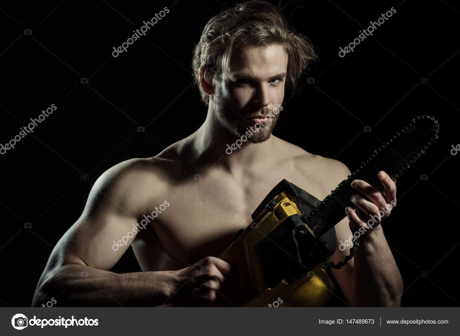 sexy man with electrical saw. naked man with a chainsaw on a black