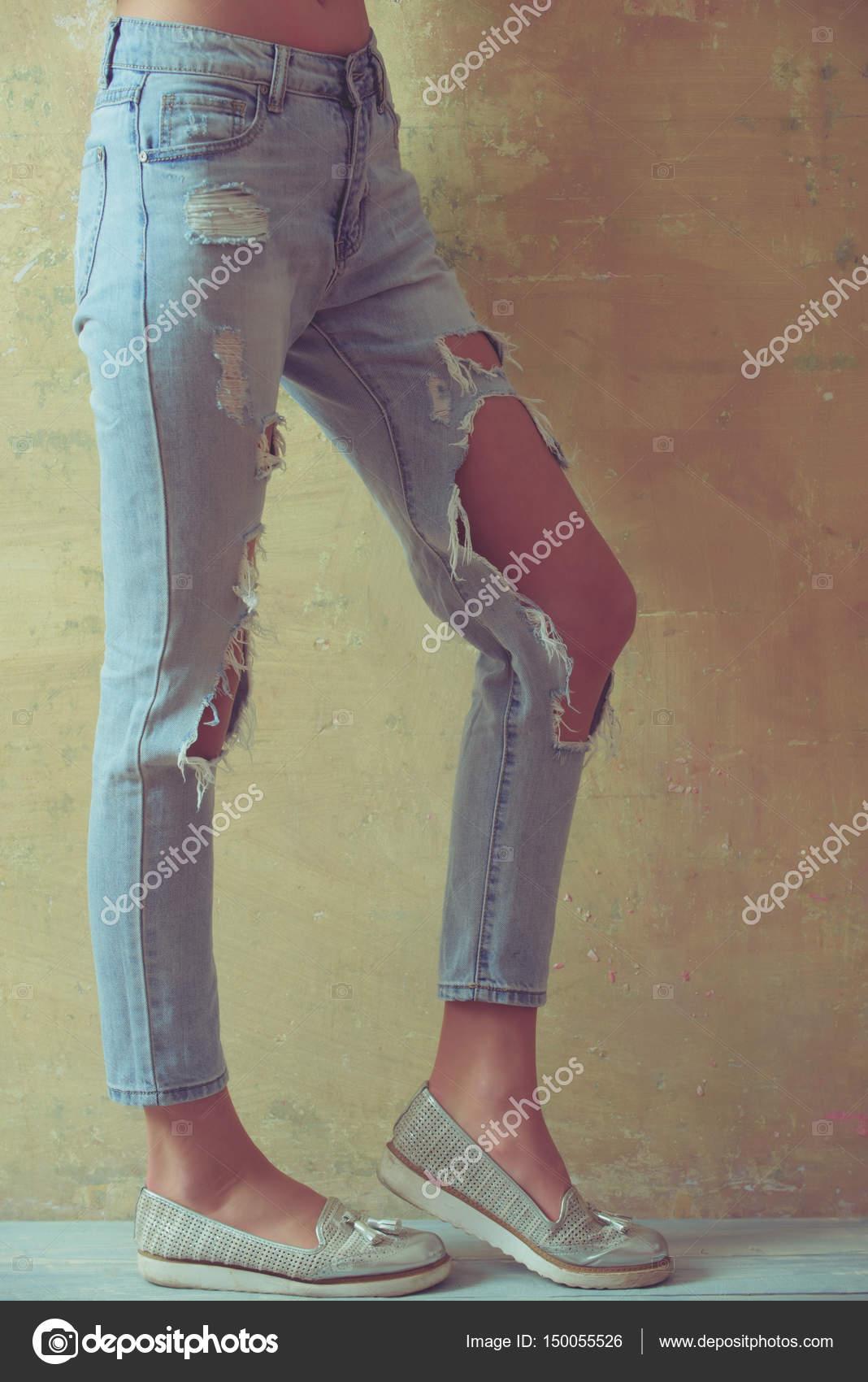 Chica hermosa en jeans rotos sobre fondo de estudio. Dama de moda arrancado  jeans se encuentra en la pared gris. Sexy mujer joven en ropa de moda sobre  ... 9d304f338870