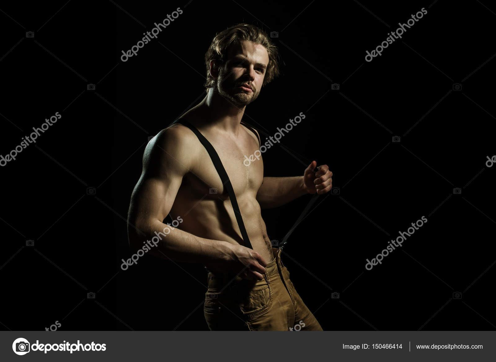 e17483a69 Hombre sexy juega con sus tirantes para pantalones sobre un fondo negro.  Hombre de moda