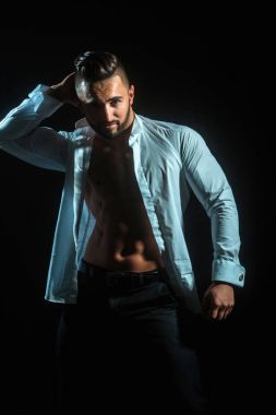 Sexy businessman on black background. Seductive and attracting man. Brunette man in white unbuttoned shirt