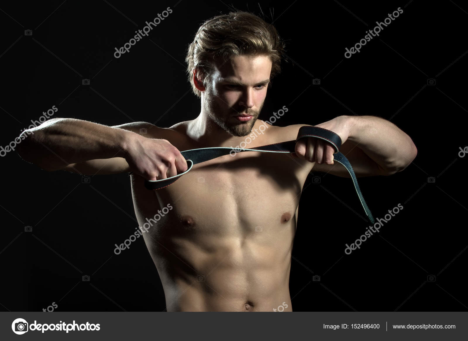 belt is in the hands of naked man. the guy does exercises for hands