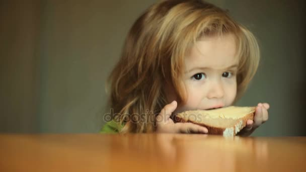 Dítě jíst sendvič chleba k snídani. Domácí chléb bez droždí kvásek a domácí máslo. Zdravé jídlo pro děti, občerstvení, roztomilý kluk na večeři u dřevěného stolu v kuchyni
