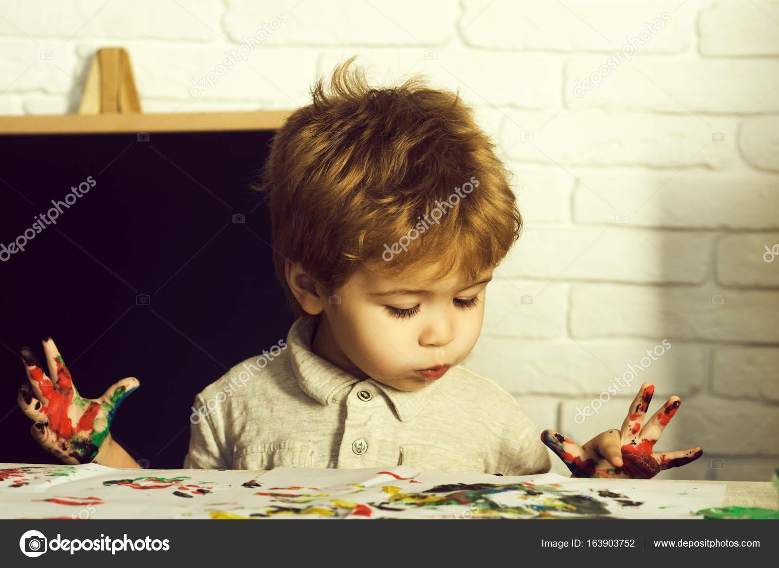 Schattig kind schilderen mooie jongen met grappige gezicht verven