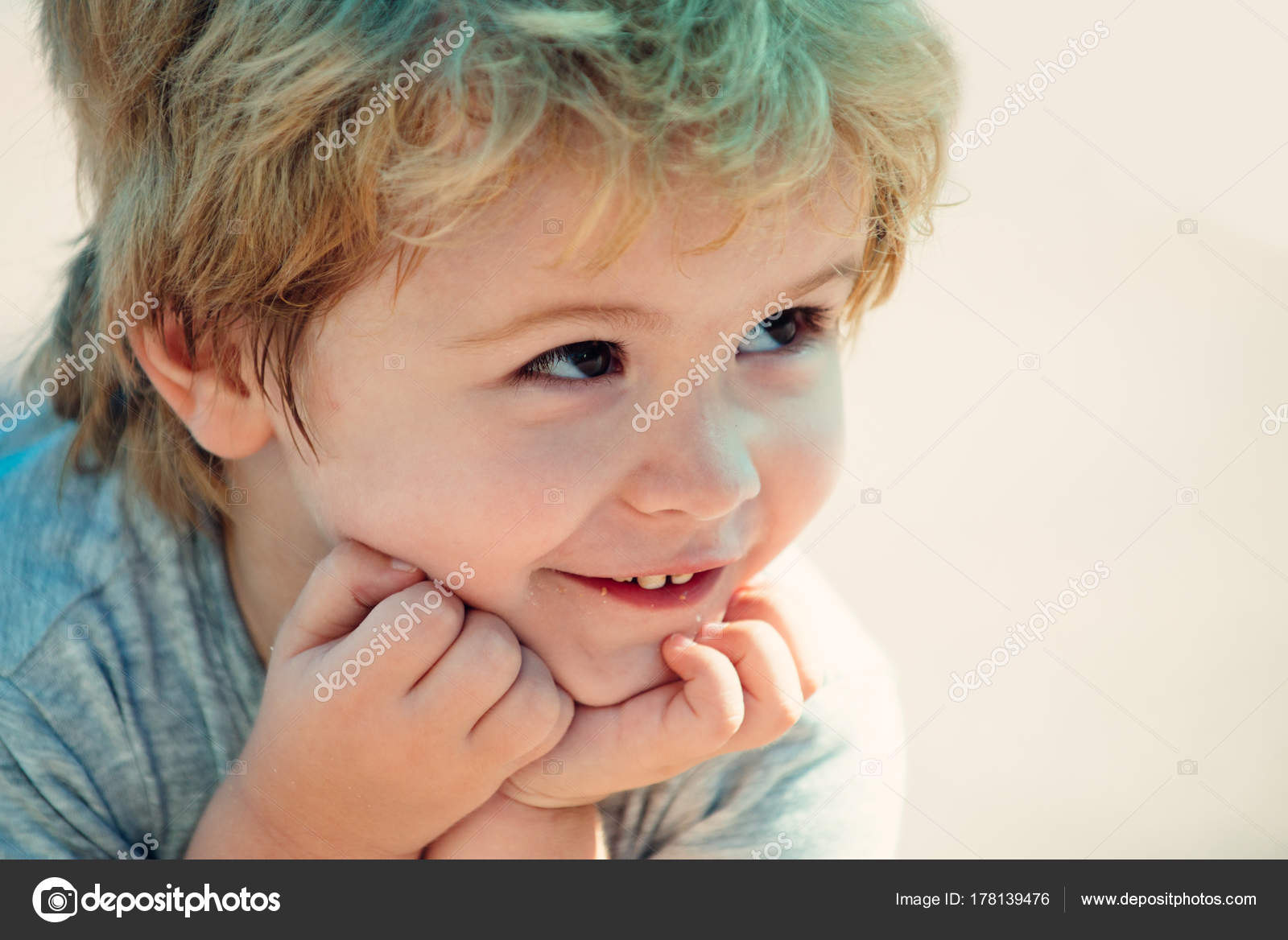 Funny baby portrait, cute boy looking up, beautiful face with white teeth and cheerful