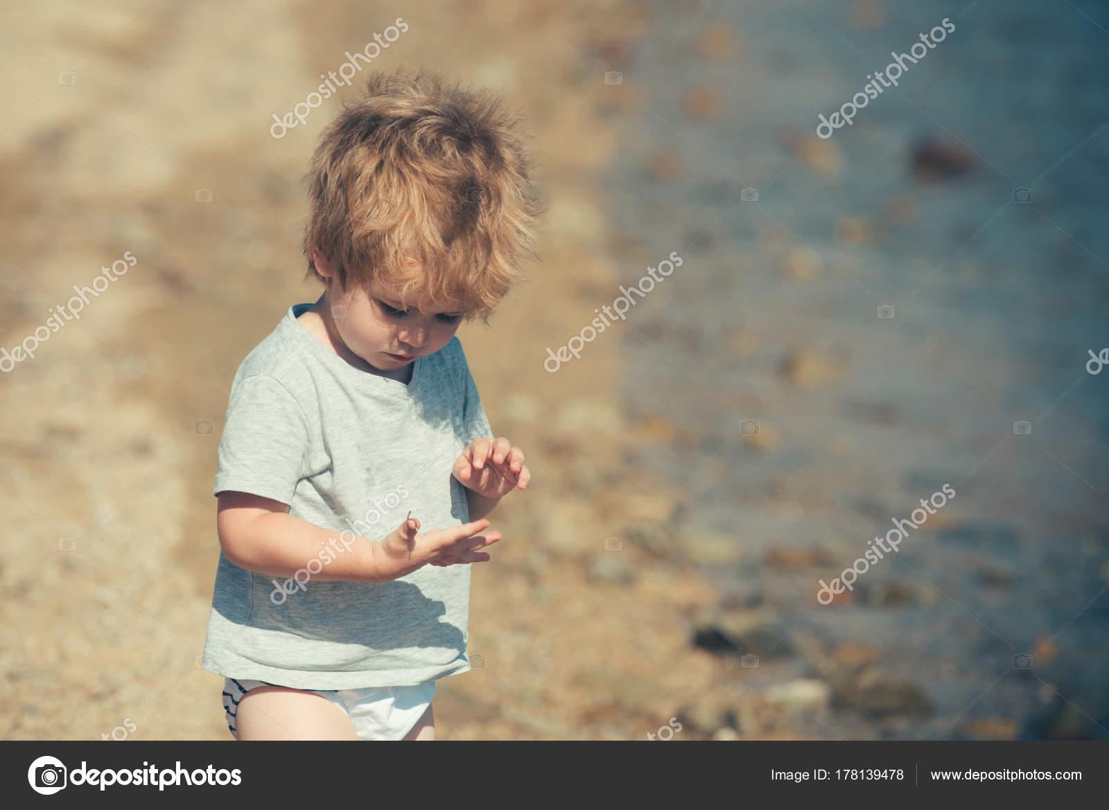 Tesoro Infantil Chico En La Playa Mira Encontrar En Su Mano