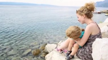 Mom with child at sea, love and care, family vacation and spending time together. Beautiful family at the sea. Beach vacation. Tourism and travel with kids. Young mother kiss son, happy childhood