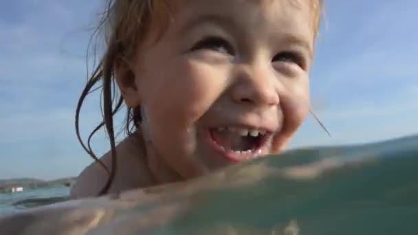 Šťastné dítě se topí v moři s pomocí matky. Lekce plavání pro malé děti. Dovolená s dětmi na moři. Rodinná Turistika, dovolená na moři. Maminka trenér, sport a plavání v dětství