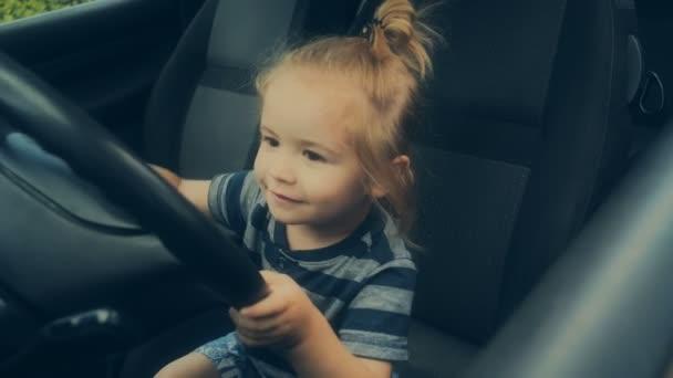 Volant, autoškolu, jako koníček. Chlapec s dlouhými vlasy má rád auta. Roztomilé dítě v autě a tatínek na předním sedadle. Bezpečnost za volantem. Osobní automobil pro děti. Baby na palubě