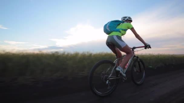 Žena cyklista jede kolo po polní cestě, pohled zezadu