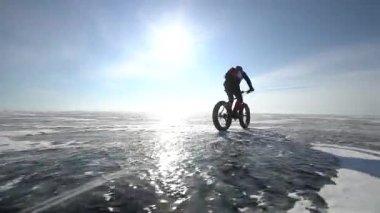 A man riding a bicycle across a frozen lake Baikal