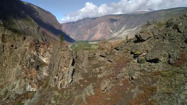 Letecké záběry. létání přes horský hřeben a údolí. skalnatý terén. útes