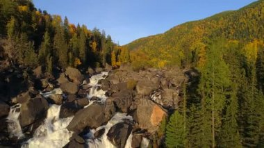 Aerial view of waterfall, flying over autumn forest, waterfall with big stones