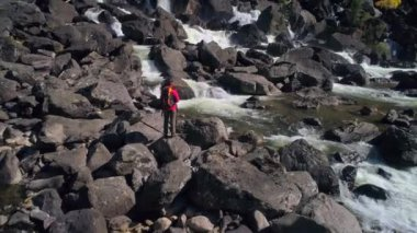 Aerial view of man standing in front of a waterfall river with rocks, river