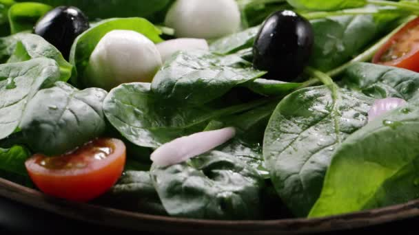 Cherry tomato falling down in fresh salad, bouncing. Green leaves, spinach, black olives, onion, mozzarella. Vegetarian food, organic food. Tasty salad. Slow motion. Full HD 240 fps