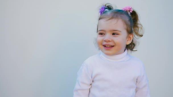 Malé roztomilé dítě se dívá do kamery a úsměv na bílém pozadí