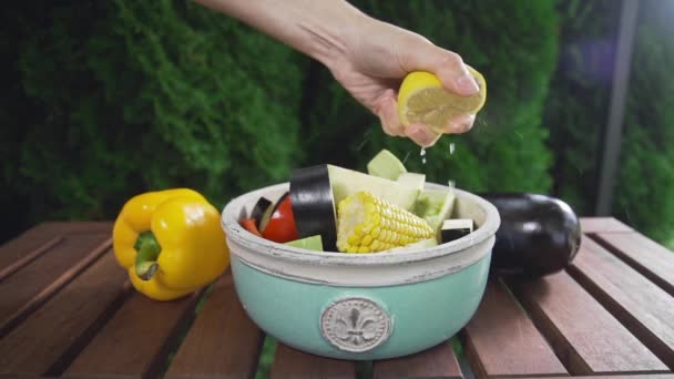 chef squeezes out lemon juice to the bowl with fresh sliced vegetables salade