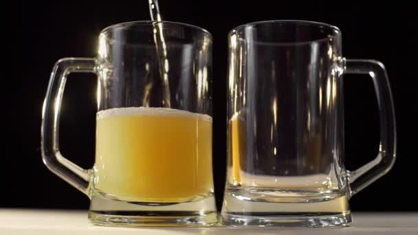 két sörös poharat öntenek habos arany világos sör fekete háttér