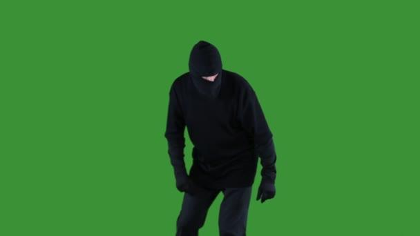 Zloděj v černou lyžařskou kuklu stopování na zelené obrazovce