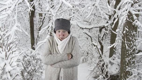 Woman sneezing into tissue, winter forest