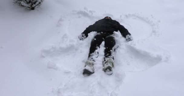 Woman making snow angels outdoor on snowy winter afternoon.
