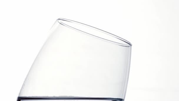 Voda teče do sklenice s cákancemi na bwhite pozadí zpomalený pohyb