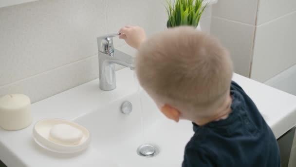 Malé dítě se naučí otevřít kohoutek vodou a umýt si ruce