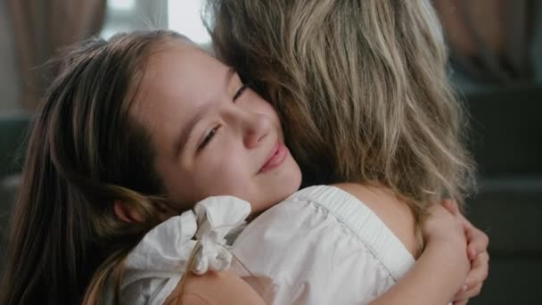 Happy cute little kid girl hugging foster care parent mother with eyes closed, adorable small child daughter embrace mum cuddling enjoy tender sweet moment close up