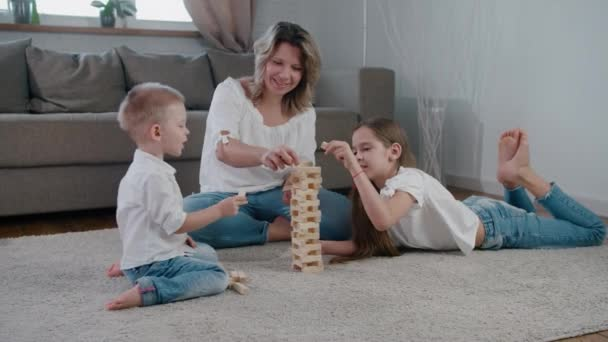 Happy family mom daughter and son have fun playing at home in the jenga. Laugh, smile and build a bright sunny day together. Slow-motion camera