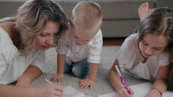 Krásná šťastná žena a mladá dívka a chlapec, matka, dcera a syn kreslit v notebooku ležící na podlaze domu jasný slunečný den. Zavřít snímek