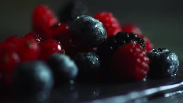 Close-up of a spray of water dripping over raspberries, blueberries and red currants. A slide of fruit lies on a plate