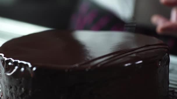 Der Koch bereitet einen Schokoladenkuchen als Zuckerguss für das Dessert zu, dekoriert seine Oberfläche mit einem Süßigkeitenkegel