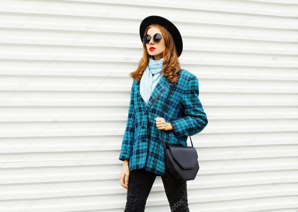 Μόδα νεαρή γυναίκα που φοράει μαύρο καπέλο παλτό καρό σακάκι τσάντα  περπατώντας στην πόλη πάνω από το λευκό φόντο — Εικόνα από Rohappy 298b624101f